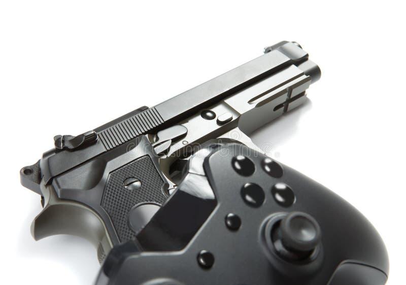 Закройте вверх по студии снятой регулятора игры и реального личного огнестрельного оружия около его - концепция виртуальных и дей стоковые фотографии rf
