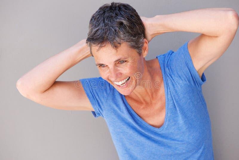 Закройте вверх по счастливой женщине смеясь над с руками за головой стоковая фотография