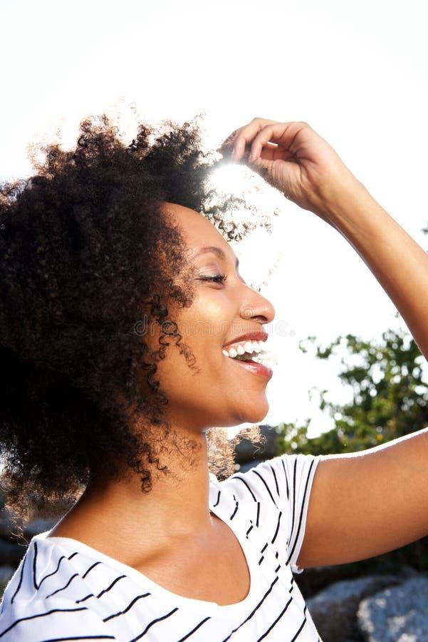 Закройте вверх по счастливой молодой чернокожей женщине с вьющиеся волосы усмехаясь outdoors стоковые фото