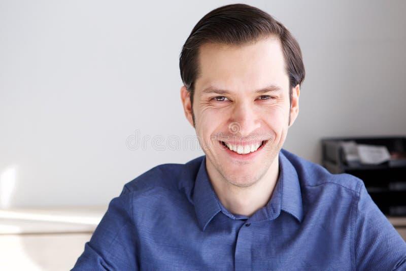Закройте вверх по счастливому уверенно предпринимателю сидя в офисе стоковая фотография rf