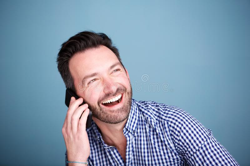 Закройте вверх по счастливому человеку говоря на мобильном телефоне и смеяться над стоковая фотография