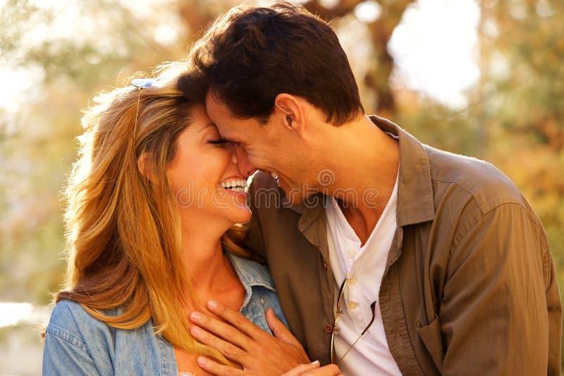 Закройте вверх по счастливым парам стоя совместно смеющся над в близком объятии стоковая фотография rf