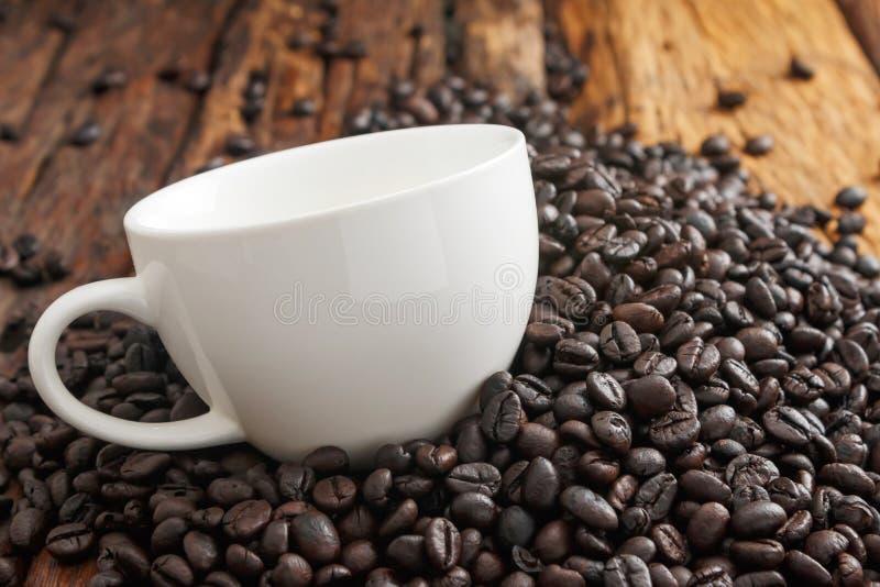 Закройте вверх по съемке белой керамической чашки на куче coffe зажаренного в духовке темнотой стоковые фото