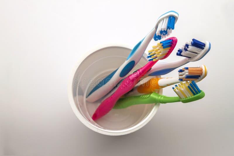 Закройте вверх по съемке комплекта пестротканых зубных щеток в стекле на cl стоковое изображение