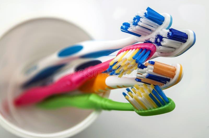 Закройте вверх по съемке комплекта пестротканых зубных щеток в стекле на cl стоковые изображения rf