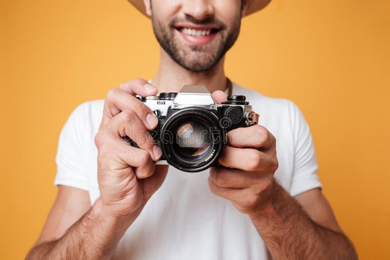 Закройте вверх по съемке молодого человека принимая фото с ретро камерой стоковая фотография rf