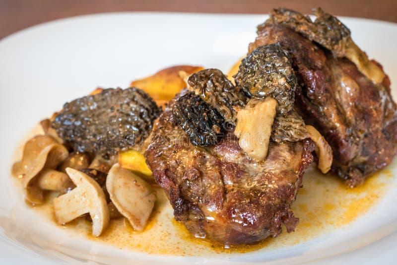 Закройте вверх по съемке плиты с испеченными свининой и грибами стоковые фотографии rf