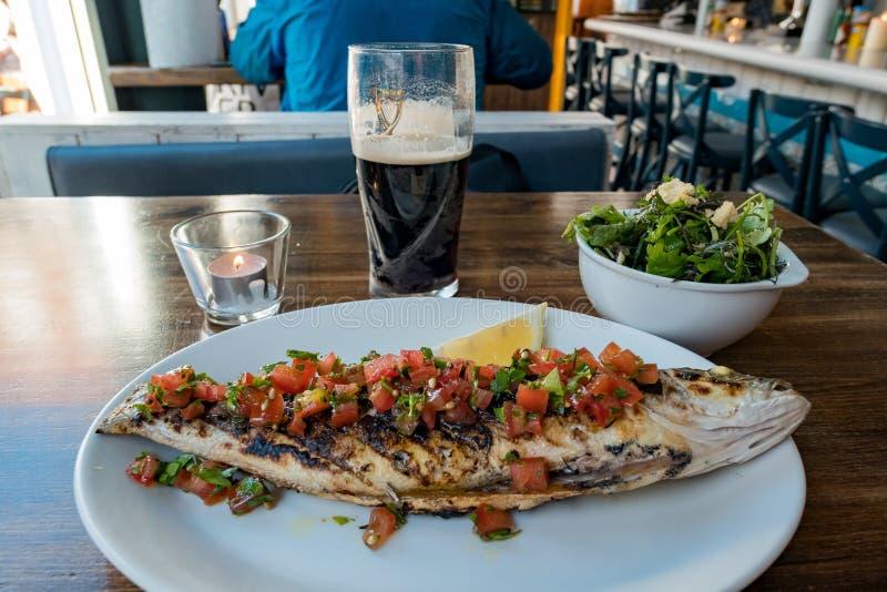 Закройте вверх по съемке стекла пива Гиннесса и морского окуня гриля стоковое изображение rf