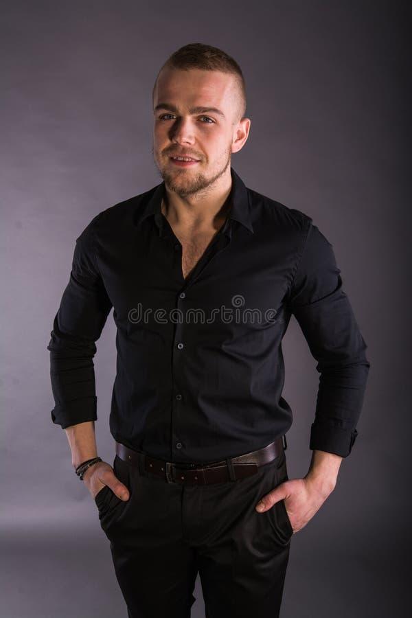 Закройте вверх по усмехаясь молодому бизнесмену нося черную рубашку и черные брюки, смотря камеру против предпосылки стены стоковая фотография rf