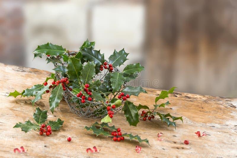 Закройте вверх по утюгу, корзине ветвей ягод падуба красных, grean листьев, вечнозелёного растения, на деревенском, таблица над a стоковые изображения rf