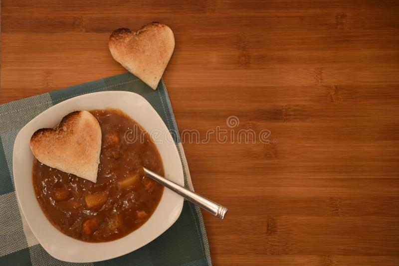 Закройте вверх по фотографии еды с надземным взглядом горячего домодельного куриного супа с здравицей формы сердца влюбленности н стоковые фотографии rf