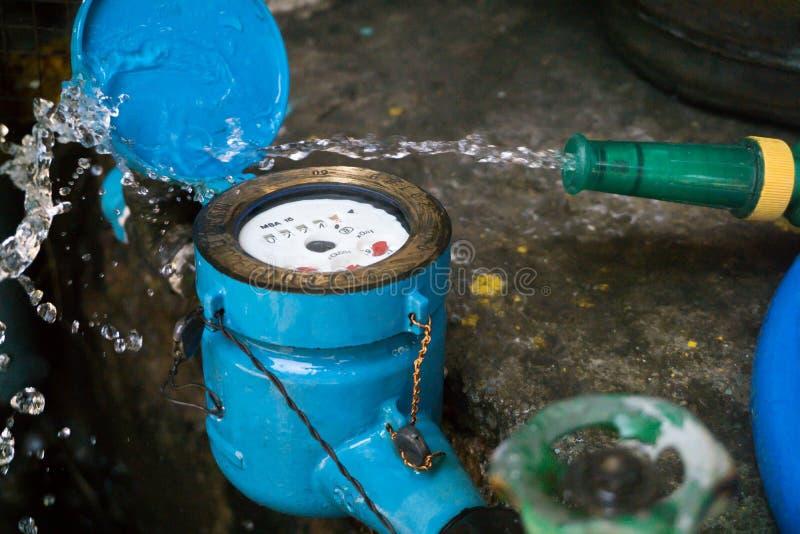 Закройте вверх по цвету сини счетчика воды И шланг с текущей водой стоковые фото