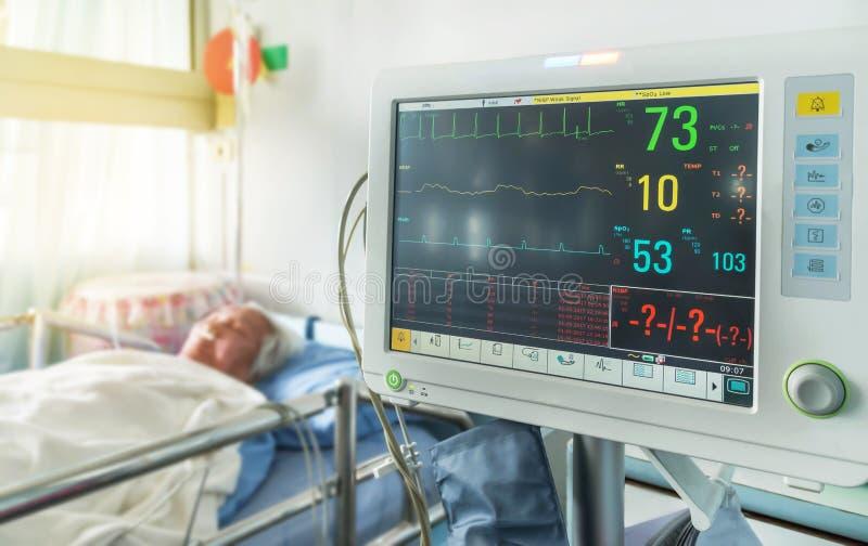 Закройте вверх по цифровому прибору для измерять монитор кровяного давления с пожилым терпеливым сном на кровати в больнице стоковая фотография