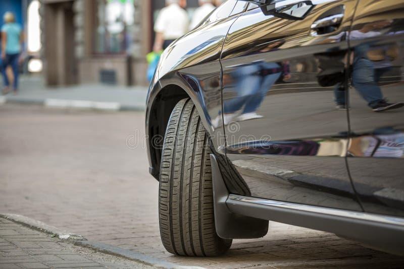 Закройте вверх по части детали колеса автомобиля с новой черной резиновой автошиной pro стоковое фото