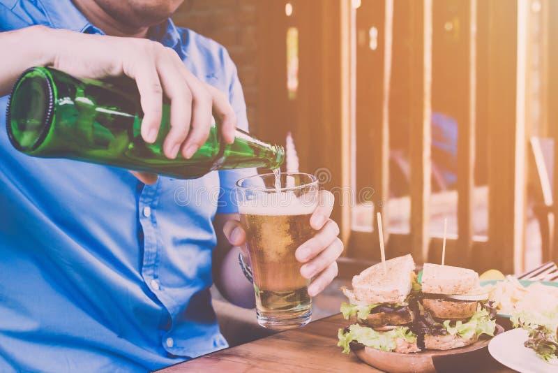 Закройте вверх по человеку в пиве голубой рубашки лить, отпразднуйте праздники пятницу стоковое изображение