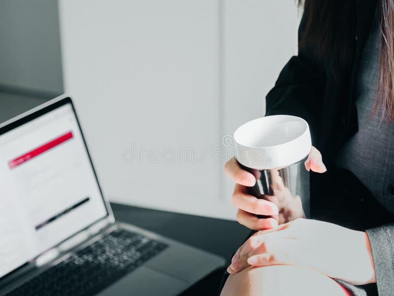 Закройте вверх по черной кофейной чашке в азиатской руке 30s бизнес-леди до 4 стоковая фотография