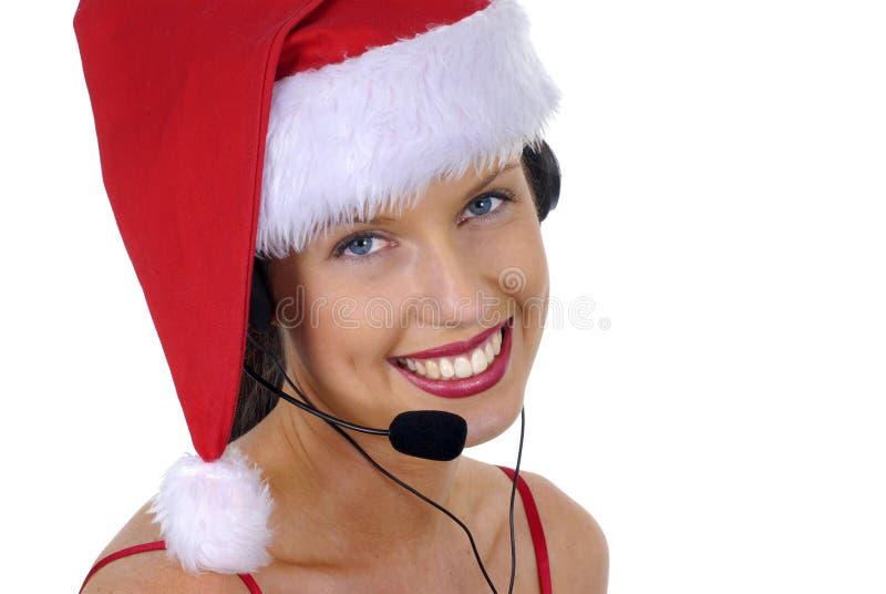 Закройте вверх привлекательного женского telephonist центра телефонного обслуживания с шляпой Санты шлемофона и рождества телефон стоковая фотография