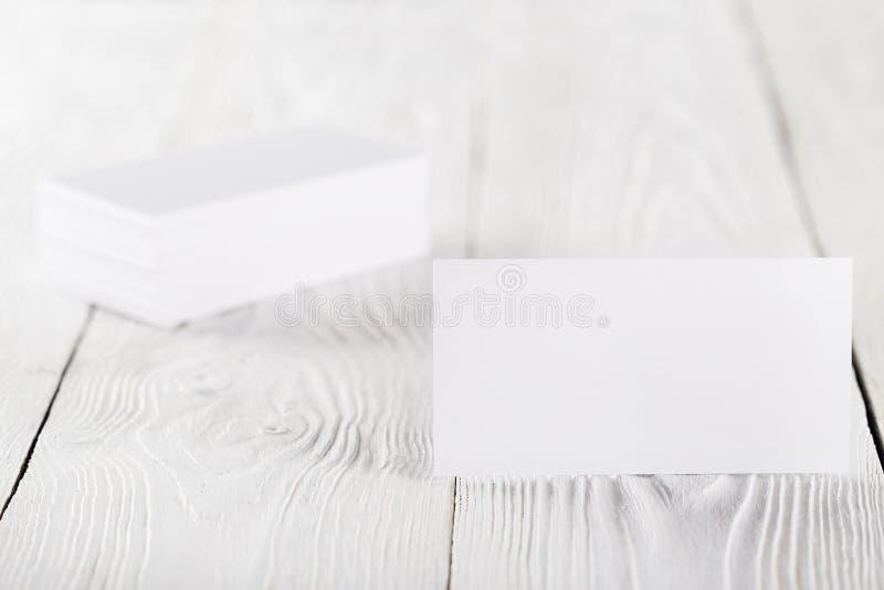 Закройте вверх 2 пустых горизонтальных визитных карточек на деревянной предпосылке стоковое изображение