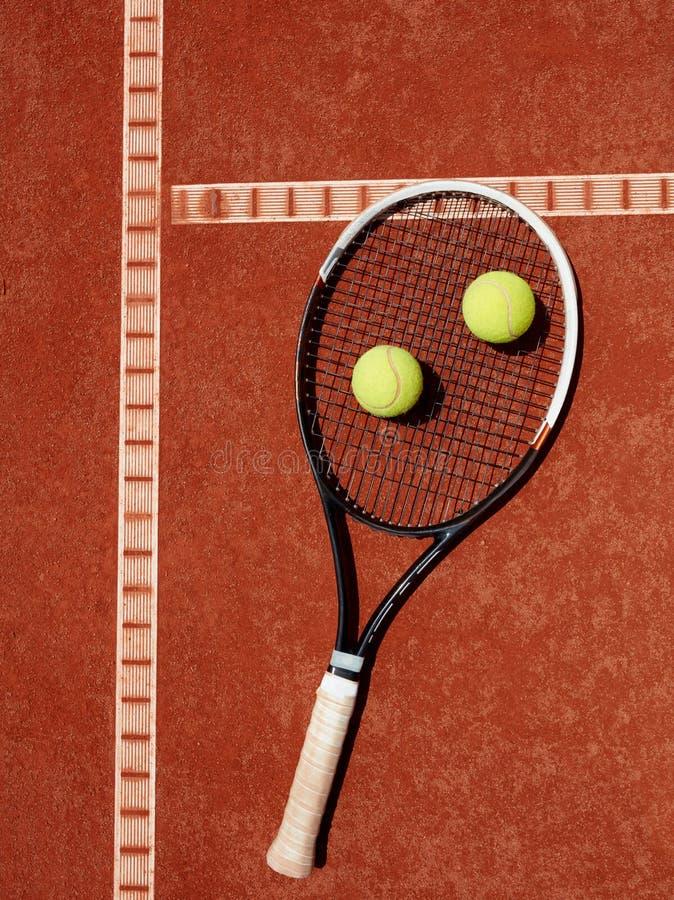 Закройте вверх ракетки тенниса и желтых шариков на красной глине стоковая фотография