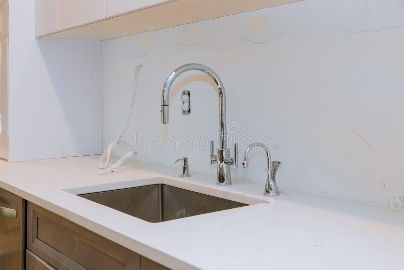 Закройте вверх раковин в современной белой кухне с белым камнем стоковая фотография