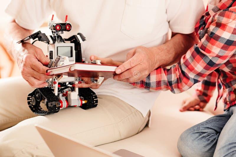Закройте вверх ребенка и grandad играя с робототехнической машиной стоковое изображение rf