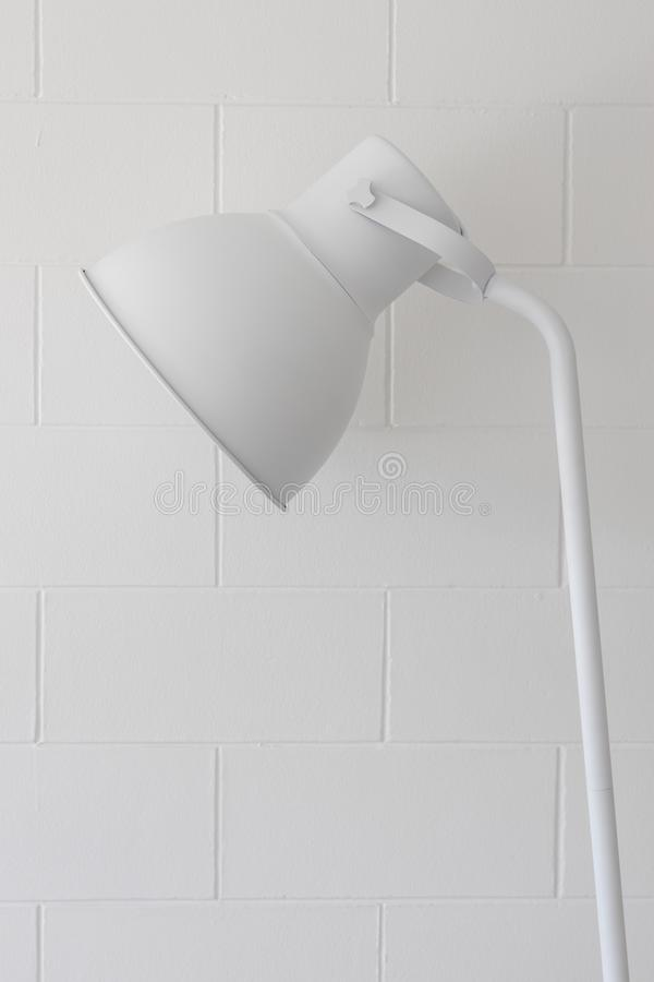 Закройте вверх регулируемой одиночной простой современной белой лампы на предпосылке текстуры кирпичной стены блока стоковое изображение