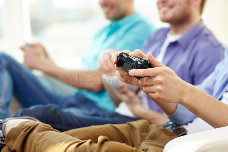 Закройте вверх друзей играя видеоигры дома стоковые фотографии rf