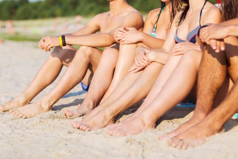 Закройте вверх друзей сидя на пляже лета стоковые фото