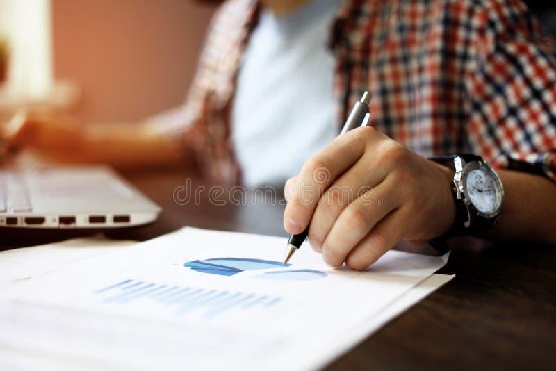 Закройте вверх руки бизнесмена работая на портативном компьютере с диаграммой данным по диаграммы дела на деревянном столе стоковое фото