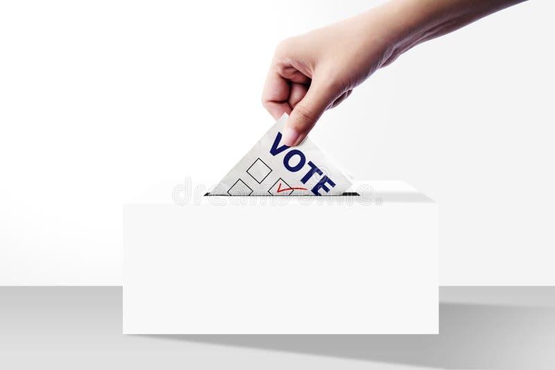 Закройте вверх руки держа бумагу голосования для голосования избрания в коробку стоковое изображение rf