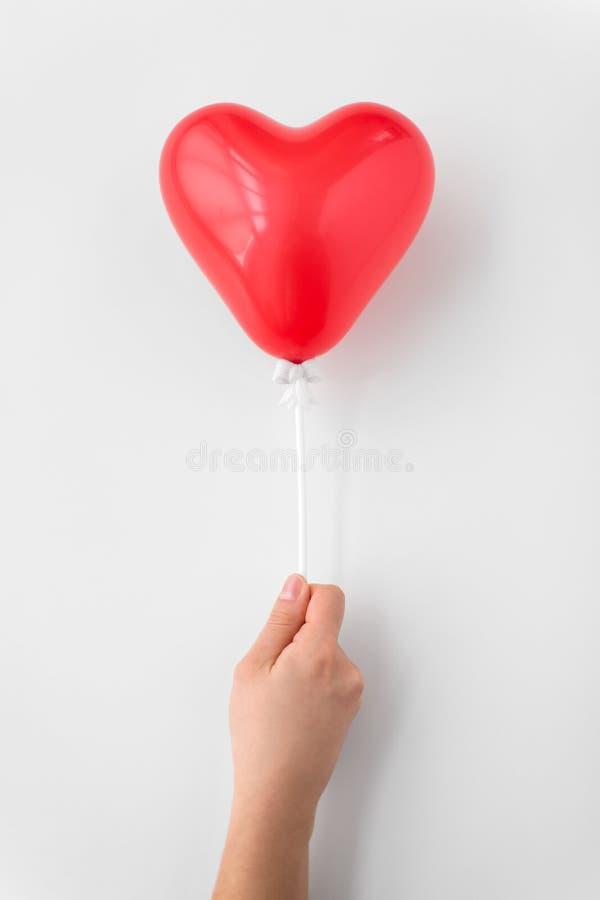 Закройте вверх руки держа воздушный шар красного сердца форменный стоковые фотографии rf