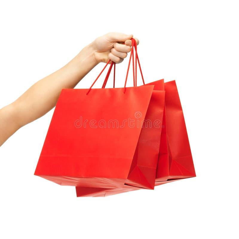 Закройте вверх руки держа красные хозяйственные сумки стоковое изображение rf