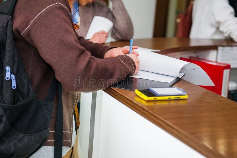 Закройте вверх руки женщины писать или подписывая внутри документ на зоне приема клиники Селективный фокус стоковые фотографии rf