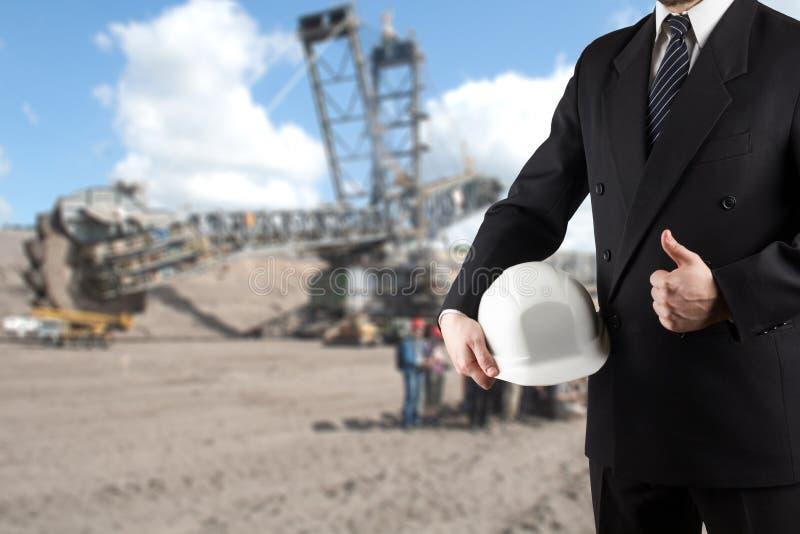 Закройте вверх руки инженера держа белый шлем безопасности для безопасности работников стоя перед запачканной строительной площад стоковые изображения