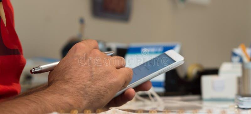 Закройте вверх руки молодого человека используя передвижной умный телефон в офисе стоковое изображение