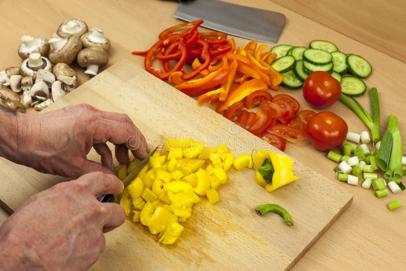 Закройте вверх руки шеф-поваров dicing желтый болгарский перец стоковая фотография