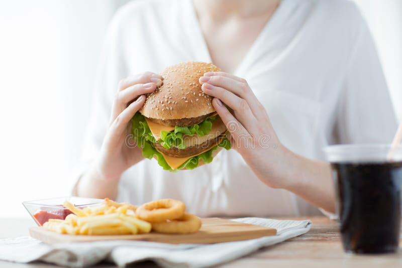 Закройте вверх рук женщины держа гамбургер стоковая фотография rf