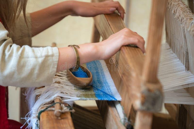 Закройте вверх рук женщины сплетя голубую и белую картину на тени Традиционный сплетя метод стоковое фото