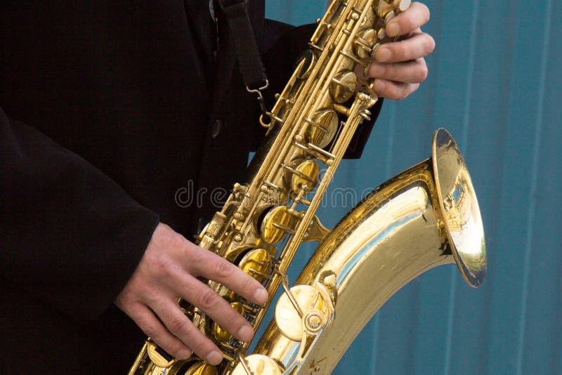 Закройте вверх рук игрока саксофона улицы играя музыкальный инструмент саксофона альта над голубой предпосылкой, крупным планом с стоковые фото