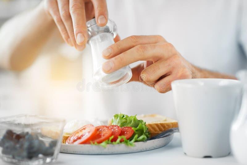 Закройте вверх рук мужчины приправляя еду мельницей соли стоковое фото