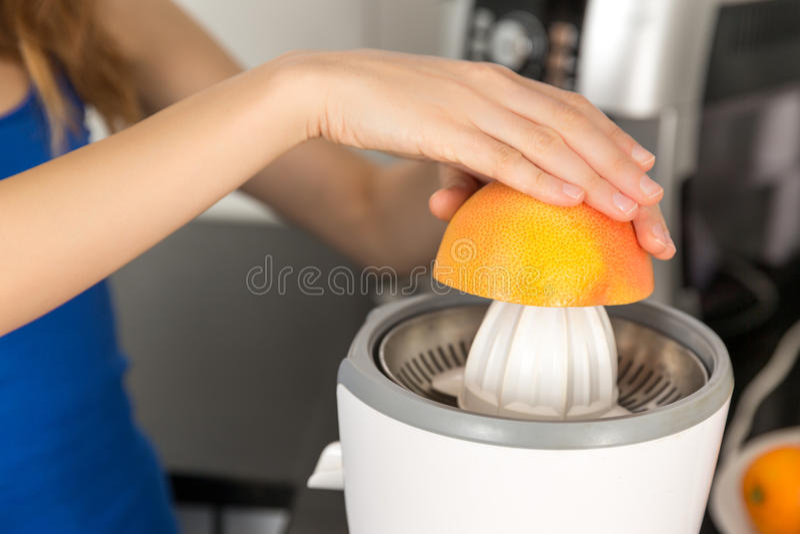 Закройте вверх рук сжимая грейпфрут стоковое фото rf