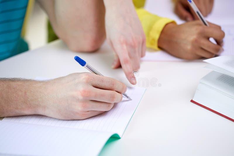 Закройте вверх рук студентов писать к тетрадям стоковые изображения
