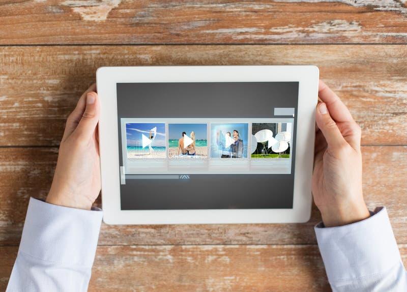 Закройте вверх рук с видео- галереей на ПК таблетки стоковое фото rf