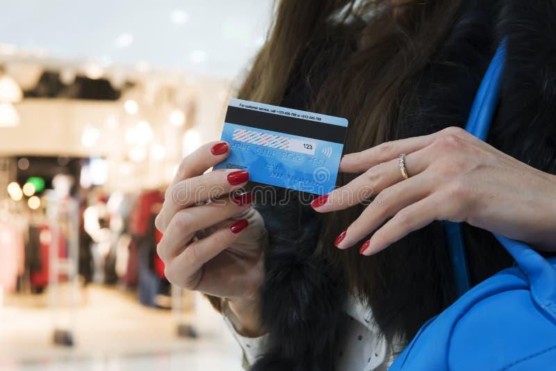 Закройте вверх рук хорошо выхоленной дамы с рыжеватым маникюром держа обратную сторону кредитной карточки на запачканном торговом стоковая фотография rf