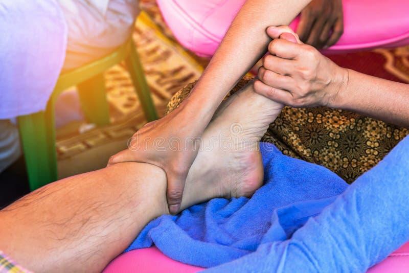 Закройте вверх рук ` s терапевта массажируя женскую ногу стоковая фотография rf