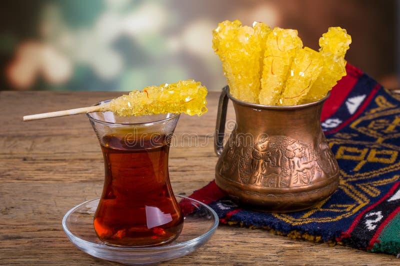 Закройте вверх сахара Кристл конфеты утеса шафрана на чашке черного чая стоковое фото rf