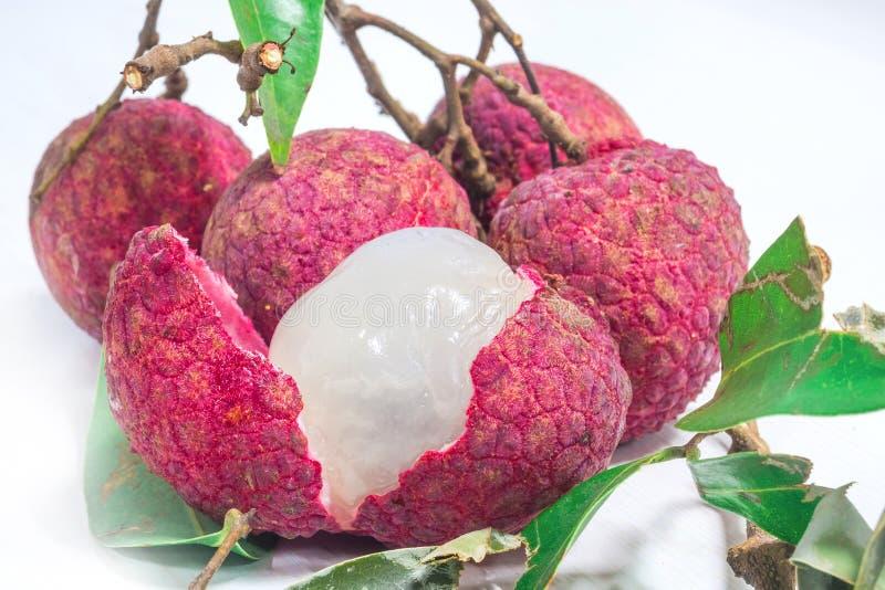Закройте вверх свежего lychee и слезанный показывающ красную плоть кожи и белых с зелеными лист стоковое изображение