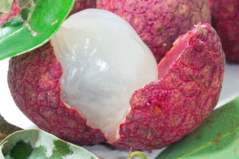 Закройте вверх свежего lychee и слезанный показывающ красную плоть кожи и белых с зелеными лист стоковая фотография