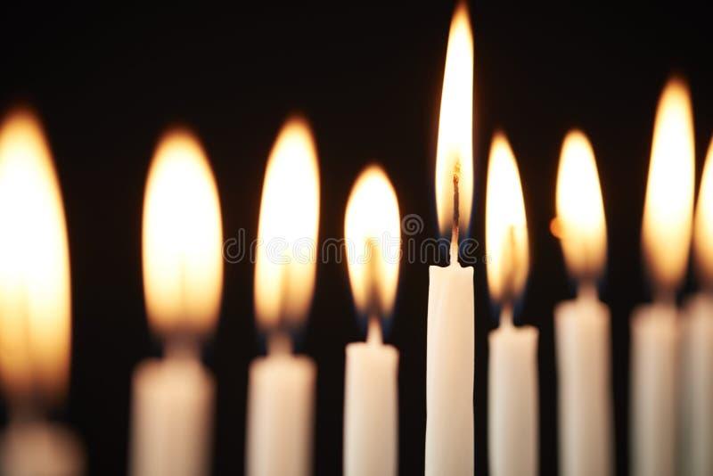 Закройте вверх свечей Lit на металле Хануке Menorah против черной предпосылки студии стоковая фотография rf
