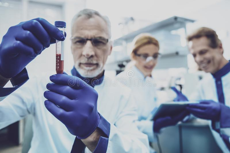 Закройте вверх серьезного ученого что рассматривающ кровь стоковые изображения rf